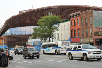 The Barclays Center looming over Brooklyn Brownstones and small shops (Copyright Argun M. Ulgen)