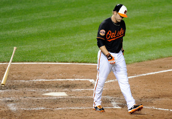 BALTIMORE, MD - AUGUST 24:  Mark Reynolds #12 of the Baltimore Orioles tosses hit bat after striking out in the sixth inning against the Toronto Blue Jays at Oriole Park at Camden Yards on August 24, 2012 in Baltimore, Maryland.  (Photo by Greg Fiume/Gett