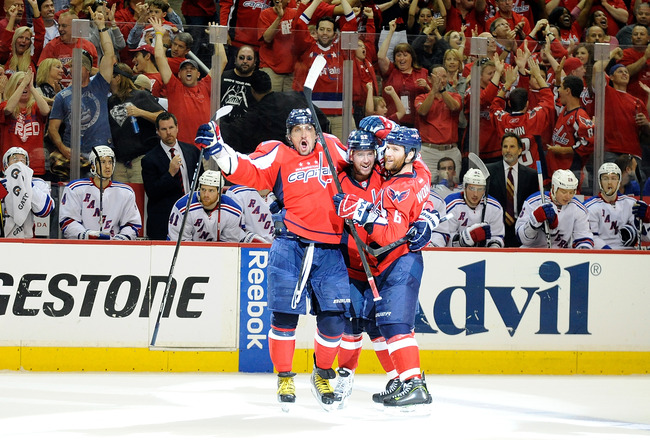 WASHINGTON, DC - MAY 05: Mike Green #52 of the Washington Capitals celebrates with Alex Ovechkin #8 and Dennis Wideman #6 after scoring the game winning goal in the third period against the New York Rangers in Game Four of the Eastern Conference Semifinal