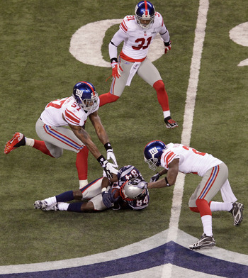 Deion Branch makes a catch between three Giants in the Super Bowl.
