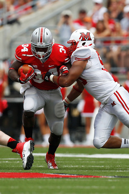 COLUMBUS, OH - SEPTEMBER 1:  Carlos Hyde #34 of the Ohio State Buckeyes is hit by Jason Semmes #93 of the Miami Redhawks during the second quarter on September 1, 2012 at Ohio Stadium in Columbus, Ohio. (Photo by Kirk Irwin/Getty Images)