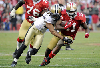 SAN FRANCISCO, CA - JANUARY 14:  Frank Gore #21 of the San Francisco 49ers gets tackled by Patrick Robinson #21 of teh New Orleans Saints in the fourth quarter during the Divisional Playoffs at Candlestick Park on January 14, 2012 in San Francisco, Califo
