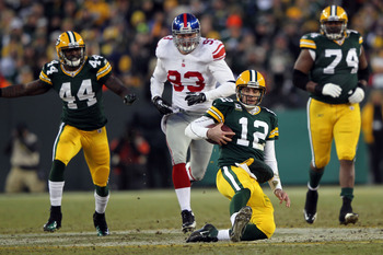 GREEN BAY, WI - JANUARY 15:   Aaron Rodgers #12 of the Green Bay Packers slides with the ball after a run against the New York Giants during their NFC Divisional playoff game at Lambeau Field on January 15, 2012 in Green Bay, Wisconsin.  (Photo by Jamie S