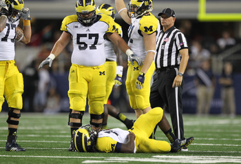 Sep 1, 2012; Arlington, TX, USA; Michigan Wolverines quarterback Denard Robinson (16) lays on the field injured in the third quarter against the Alabama Crimson Tide at Cowboys Stadium. Mandatory Credit: Matthew Emmons-US PRESSWIRE