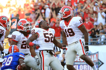 October 29, 2011; Jacksonville FL, USA; Georgia Bulldogs linebacker Amarlo Herrera (52) reacts after tackling Florida Gators running back Jeff Demps (28) during the second half at EverBank Field. Georgia Bulldogs defeated the Florida Gators 24-20. Mandato