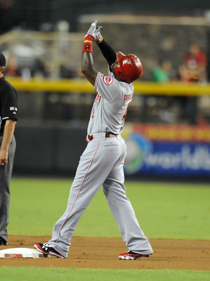 PHOENIX, AZ - AUGUST 28:  Brandon Phillips #4 of the Cincinnati Reds points to the sky after reaching second base against the Arizona Diamondbacks at Chase Field on August 28, 2012 in Phoenix, Arizona.  (Photo by Norm Hall/Getty Images)