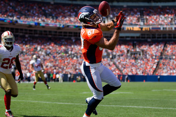DENVER, CO - AUGUST 26:  Wide receiver Eric Decker #87 of the Denver Broncos makes a catch for a touchdown as cornerback Tramaine Brock #26 of the San Francisco 49ers looks on during the first quarter of a pre-season game at Sports Authority Field Field a