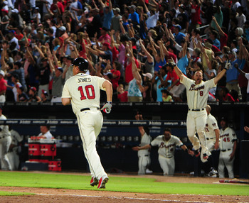 ATLANTA, GA - SEPTEMBER 2: David Ross #8 celebrates in the background as Chipper Jones #10 of the Atlanta Braves runs the bases after hitting a three-run walk-off home run against the Philadelphia Phillies at Turner Field on September 2 2012 in Atlanta, G