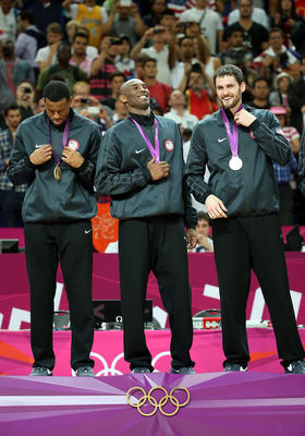 LONDON, ENGLAND - AUGUST 12:  Andre Iguodala #9, Kobe Bryant #10 and Kevin Love #11 of United States stand on the podium with their gold medals after defeating Spain in the Men's Basketball gold medal game on Day 16 of the London 2012 Olympics Games at No
