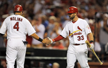 ST. LOUIS, MO - SEPTEMBER 4: Daniel Descalso #33 of the St. Louis Cardinals congratulates Yadier Molina #4 after he scored against the New York Mets at Busch Stadium on September 4, 2012 in St. Louis, Missouri. (Photo by Jeff Curry/Getty Images)