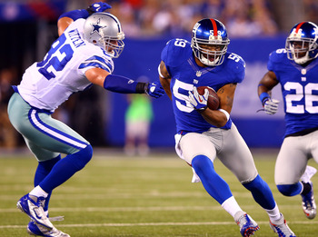 EAST RUTHERFORD, NJ - SEPTEMBER 05:  Linebacker Michael Boley #59 of the New York Giants runs with the ball after an interception in the second quarter as tight end Jason Witten #82 of the Dallas Cowboys tries to tackle him during the 2012 NFL season open