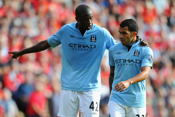 LIVERPOOL, ENGLAND - AUGUST 26:  Yaya Toure of Manchester City speaks to team mate Carlos Tevez (R) during the Barclays Premier League match between Liverpool and Manchester City at Anfield on August 26, 2012 in Liverpool, England.  (Photo by Michael Rega