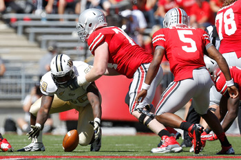 COLUMBUS, OH - SEPTEMBER 8:  Troy Davis #58 of the Central Florida Knights covers up a loose ball before Jack Mewhort #74 of the Ohio State Buckeyes is able to fall on it during the fourth quarter on September 8, 2012 at Ohio Stadium in Columbus, Ohio. Oh