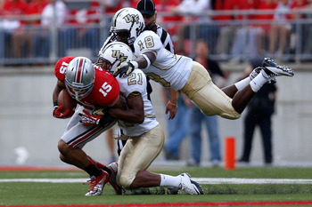 COLUMBUS, OH - SEPTEMBER 8:  Devin Smith #15 of the Ohio State Buckeyes is tackled by A.J. Bouye #21 and Kemal Ishmael #18, both of the Central Florida Knights, during the fourth quarter on September 8, 2012 at Ohio Stadium in Columbus, Ohio. Ohio defeate
