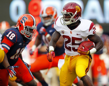 EAST RUTHERFORD, NJ - SEPTEMBER 8: Silas Redd #25 of the USC Trojans looks for an opening to run as Siriki Diabate #18 of the Syracuse Orange closes in during a game at MetLife Stadium on September 8, 2012 in East Rutherford, New Jersey. (Photo by Rich Sc