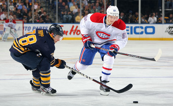 Lars Eller looks to skate past Corey Tropp of the Buffalo Sabres.