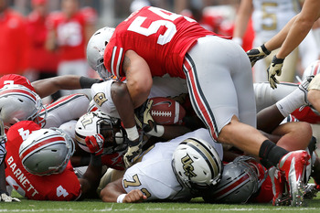 COLUMBUS, OH - SEPTEMBER 8:  Storm Johnson #8 of the Central  Florida Knights is tackled by John Simon #54 of the Ohio State Buckeyes and C.J. Barnett #4 of the Ohio State Buckeyes during the third quarter on September 8, 2012 at Ohio Stadium in Columbus,