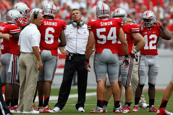 COLUMBUS, OH - SEPTEMBER 1:  Head Coach Urban Meyer of the Ohio State Buckeyes watches a reply while meeting with members of his defense during a timeout on September 1, 2012 at Ohio Stadium in Columbus, Ohio. Ohio State defeated Miami 56-10. (Photo by Ki