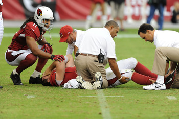 Trainers tend to Skelton while Larry Fitzgerald comforts him.