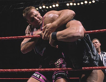 Owen Hart works over Steve Austin. Photo credit WWE.