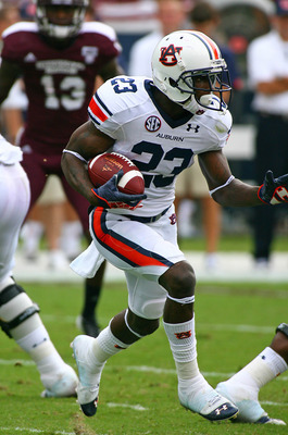 Sept 8, 2012; Starkville, MS, USA;   Auburn Tigers running back Onterio McCalebb (23) runs the ball for extra yardage at Davis Wade Stadium. Mandatory Credit: Spruce Derden�US PRESSWIRE