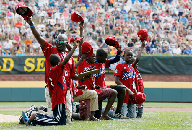 SOUTH WILLAMSPORT, PA - AUGUST 26: Members of team Uganda wave to the crowd after being acknowledged before the start of the championship game of the Little League World Series on August 26, 2012 in South Willamsport, Pennsylvania.  (Photo by Rob Carr/Get