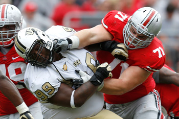 COLUMBUS, OH - SEPTEMBER 8:  Corey Linsley #71 of the Ohio State Buckeyes blocks Jose Jose #99 of the Central Florida Knights during the second quarter on September 8, 2012 at Ohio Stadium in Columbus, Ohio. (Photo by Kirk Irwin/Getty Images)