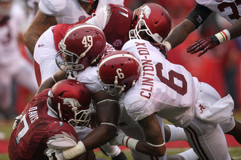Sep 15, 2012; Fayetteville, AR, USA; Alabama Crimson Tide defensive lineman Ed Stinson (49) and defensive back Ha'Sean Clinton-Dixon (6) tackle Arkansas Razorbacks running back Knile Davis (7) during the second quarter at Donald W. Reynolds Razorback Stad