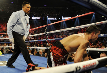 Referee Tony Weeks looks to start the 10-count on a fallen Martinez.