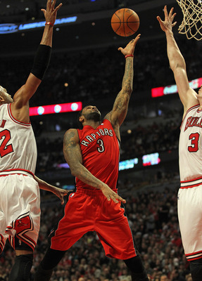 CHICAGO, IL - MARCH 24:  Gary Forbes #3 of the Toronto Raptors shoots between Taj Gibson #22 and Omer Asik #3 of the Chicago Bulls at the United Center on March 24, 2012 in Chicago, Illinois. NOTE TO USER: User expressly acknowledges and agrees that, by d