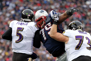 FOXBORO, MA - JANUARY 22:   Joe Flacco #5 of the Baltimore Ravens gets tackled by  Vince Wilfork #75 of the New England Patriots during their AFC Championship Game at Gillette Stadium on January 22, 2012 in Foxboro, Massachusetts.  (Photo by Jim Rogash/Ge