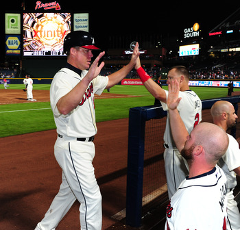 ATLANTA, GA - SEPTEMBER 16: Chipper Jones #10 of the Atlanta Braves is congratulated by teammates after scoring a seventh inning run against the Washington Nationals at Turner Field on September 16, 2012 in Atlanta, Georgia. (Photo by Scott Cunningham/Get