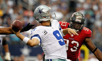 ARLINGTON, TX - SEPTEMBER 23:   Tony Romo #9 of the Dallas Cowboys looks for an open receiver under pressure from  Gerald McCoy #93 of the Tampa Bay Buccaneers at Cowboys Stadium on September 23, 2012 in Arlington, Texas. The Dallas Cowboys beat the Tampa