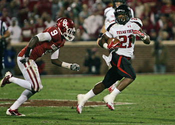 NORMAN, OK - OCTOBER 22:  Running back DeAndre Washington of Texas Tech tries to outrun defensive back Gabe Lynn #9 during the second half at at Gaylord Family-Oklahoma Memorial Stadium on October 22, 2011 in Norman, Oklahoma.  Oklahoma was upset by Texas