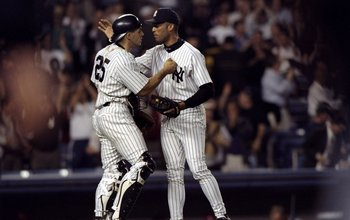 Former New York Yankees catcher Joe Girardi embraces Mariano Rivera.
