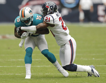 HOUSTON,TX - SEPTEMBER 09: Davone Bess #15 of the Miami Dolphins is tackled by Brice McCain #21 of the Houston Texans during the season opener at Reliant Stadium on September 9, 2012 in Houston, Texas.  (Photo by Bob Levey/Getty Images)
