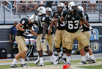 ORLANDO, FL - SEPTEMBER 15:  Receiver J.J. Worton #9 of the Central Florida Knights is congratulated by his teammates after his touchdown against the Florida International Panthers during the game at Bright House Networks Stadium on September 15, 2012 in