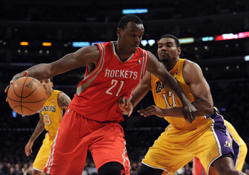 LOS ANGELES, CA - APRIL 06:  Samuel Dalembert #21 of the Houston Rockets dribbles to the basket in front of Andrew Bynum #17 of the Los Angeles Lakers at Staples Center on April 6, 2012 in Los Angeles, California.  NOTE TO USER: User expressly acknowledge