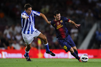BARCELONA, SPAIN - AUGUST 19:  Lionel Messi of FC Barcelona (R) duels for the ball with Ion Ansotegi Gorostola of Real Sociedad during the La Liga match between FC Barcelona and Real Sociedad de Futbol at Camp Nou on August 19, 2012 in Barcelona, Spain.