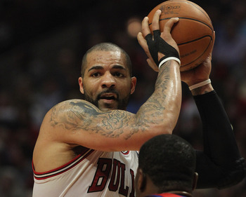 CHICAGO, IL - MAY 08:  Carlos Boozer #5 of the Chicago Bulls looks to pass against Elton Brand #42 of the Philadelphia 76ers in Game Five of the Eastern Conference Quarterfinals during the 2012 NBA Playoffs at the United Center on May 8, 2012 in Chicago,