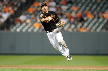 BALTIMORE, MD - AUGUST 24:  J.J. Hardy #2 of the Baltimore Orioles throws the ball to first base for an out in the ninth inning against the Toronto Blue Jays at Oriole Park at Camden Yards on August 24, 2012 in Baltimore, Maryland. Baltimore won the game 