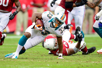 Calais Campbell (bottom) drags down Daniel Thomas of Miami.