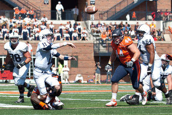 Sep 29, 2012; Champaign, IL, USA; Penn State Nittany Lions quarterback Matthew McGloin (11) throws the ball while avoiding a tackle by Illinois Fighting Illini linebacker Ashante Williams (25) during the third quarter at Memorial Stadium. Mandatory Credit
