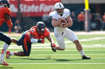 Sep 29, 2012; Champaign, IL, USA; Penn State Nittany Lions running back Zach Zwinak (28) tries to avoid a tackle by Illinois Fighting Illini defensive lineman Glenn Foster (91) during the second quarter at Memorial Stadium. Mandatory Credit: Bradley Leeb-