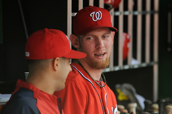Stephen Strasburg converses with teammate Gio Gonzalez in the dugout during a Sept. 22 game against the Milwaukee Brewers