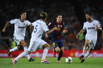 BARCELONA, SPAIN - AUGUST 23: Lionel Messi of FC Barcelona (2ndR) duels for the ball with Cristiano Ronaldo, Fabio Coentrao (2ndL) and Xabi Alonso of Real Madrid CF during the Super Cup first leg match between FC Barcelona and Real Madrid at Camp Nou on A
