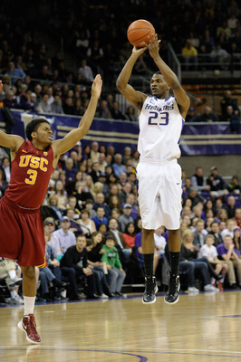 Feb 4, 2012; Seattle, WA, USA; Washington Huskies guard C.J. Wilcox (23) shoots three pointer while USC Trojans guard Alexis Moore (3) tries to block the shot during the 1st half at Alaska Airlines Arena. Mandatory Credit: Steven Bisig-US PRESSWIRE
