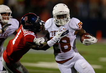 OXFORD, MS - SEPTEMBER 15:  Malcolm Brown #28 of the Texas Longhorns fights off the tackle of Dehendret Collins #1 of the Ole Miss Rebels at Vaught-Hemingway Stadium on September 15, 2012 in Oxford, Mississippi.  (Photo by Scott Halleran/Getty Images)