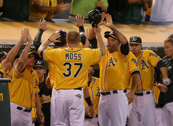 The Oakland A's congratulate their teammate Brandon Moss after he scores in Tuesday's game against the Texas Rangers.