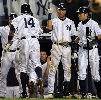 New York Yankees Derek Jeter and Ichiro Suzuki wait for Curtis Granderson at the plate as he scores against the Boston Red Sox Tuesday night.